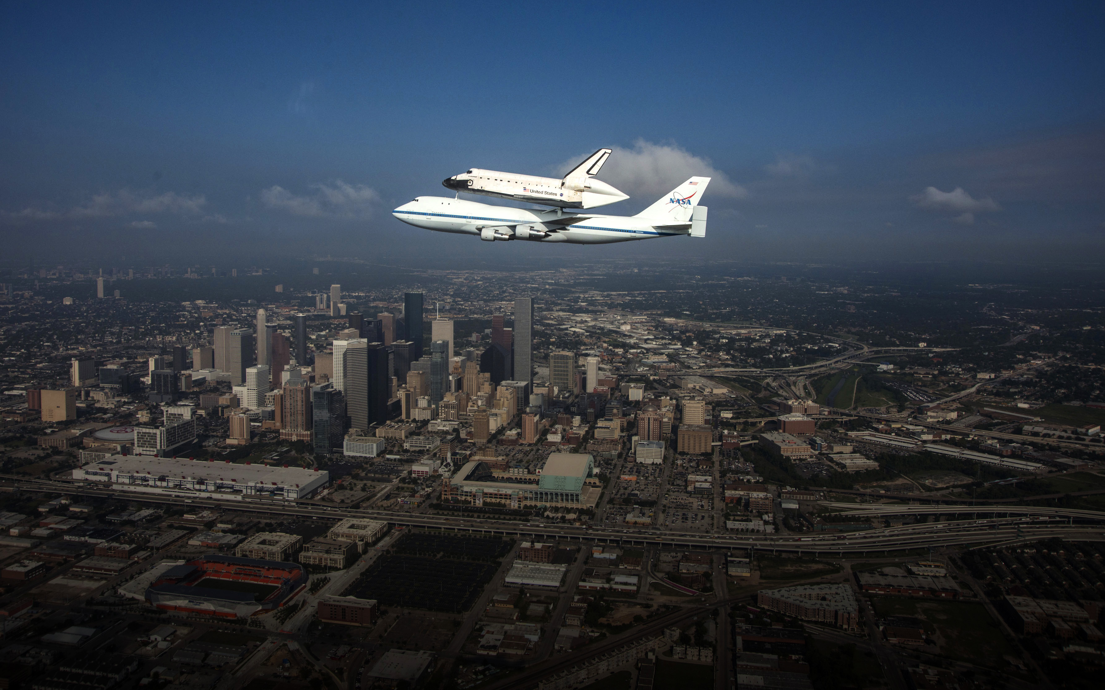 The shuttle carrier aircraft flies over Houston.