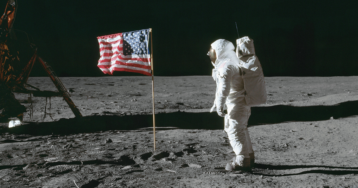 Astronaut Edwin E. Aldrin,Lunar Module (LM) pilot, poses for a photo beside the U.S. flag that has been placed on the moon. The LM is visible in the left  field of view. Numerous footprints and the cable of the surface television camera are visible on the lunar surface in the foreground.  Image taken at Tranquility Base during the Apollo 11 Mission. Original film magazine was labeled S.  Film Type: Ektachrome EF SO168 color film on a 2.7-mil Estar polyester base taken with a 60mm lens. Sun angle is Medium. Tilt direction is South (S).