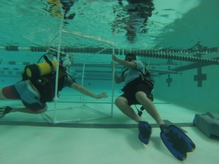 Students assemble PVC frame underwater