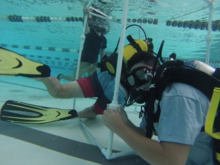A student works to assemble a PVC frame underwater