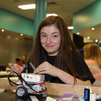 A Space Center U student shows off her robot