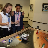 Two students successfully traverse the space field with their newly coded robot