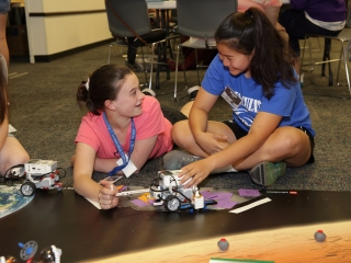 Two students work together to successfully code their robot