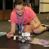 A Space Center U student attempts to traverse a space field with her newly designed robot