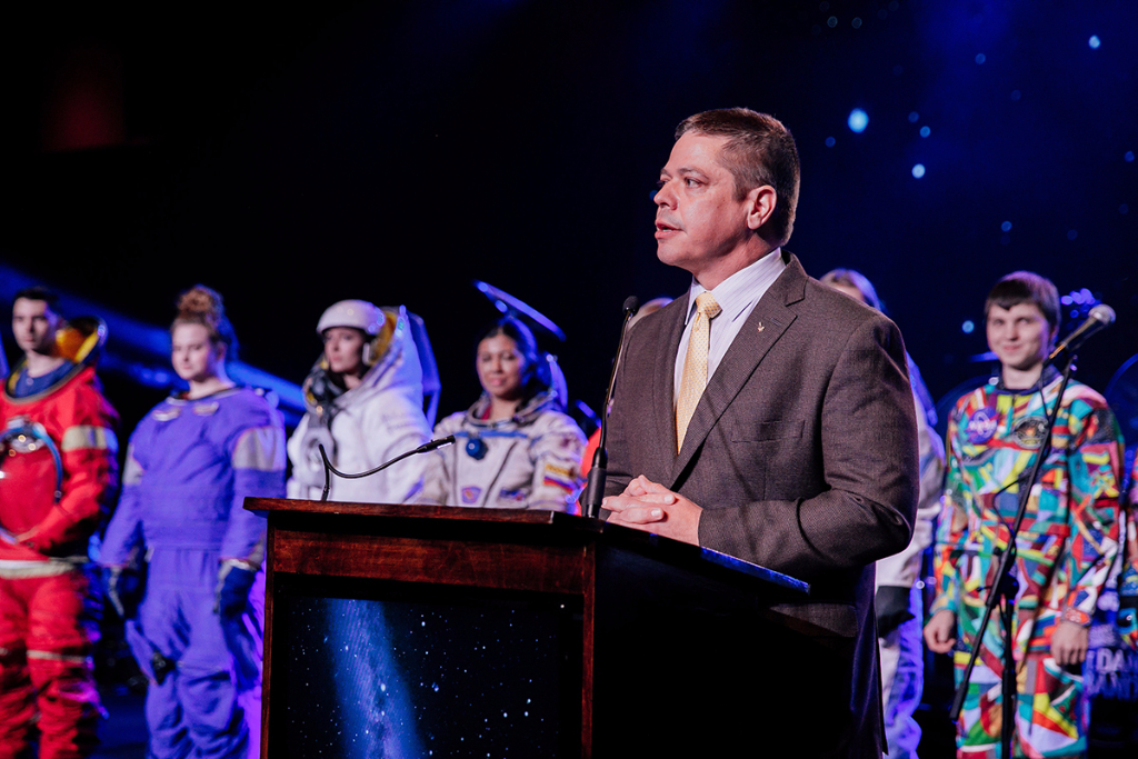 A speaker with spacesuits in the background.