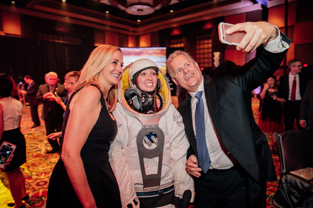 VIP guests snap a selfie with a NASA spacesuit.