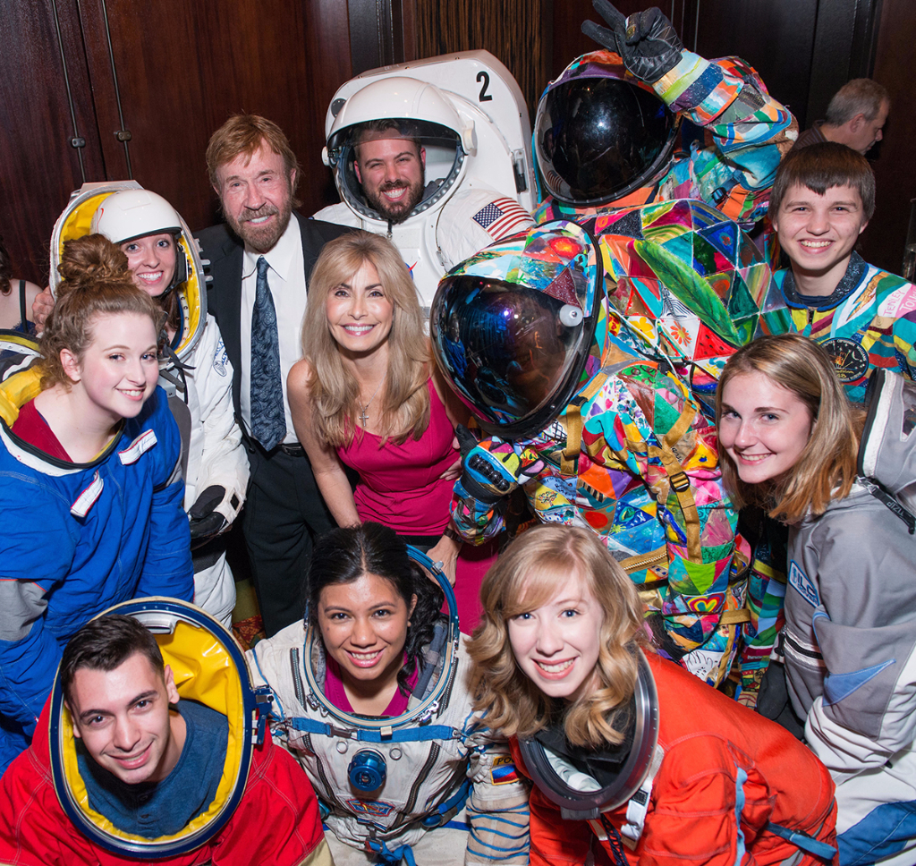 Chuck Norris and his wife, Gena, take a group picture with all the spacesuit models!