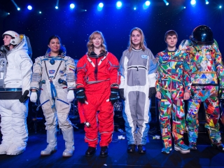 Spacesuit models stand together for a photo on stage.