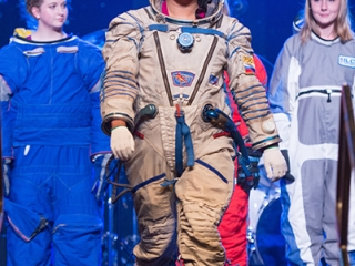 A model walks the stage to show off her spacesuit.
