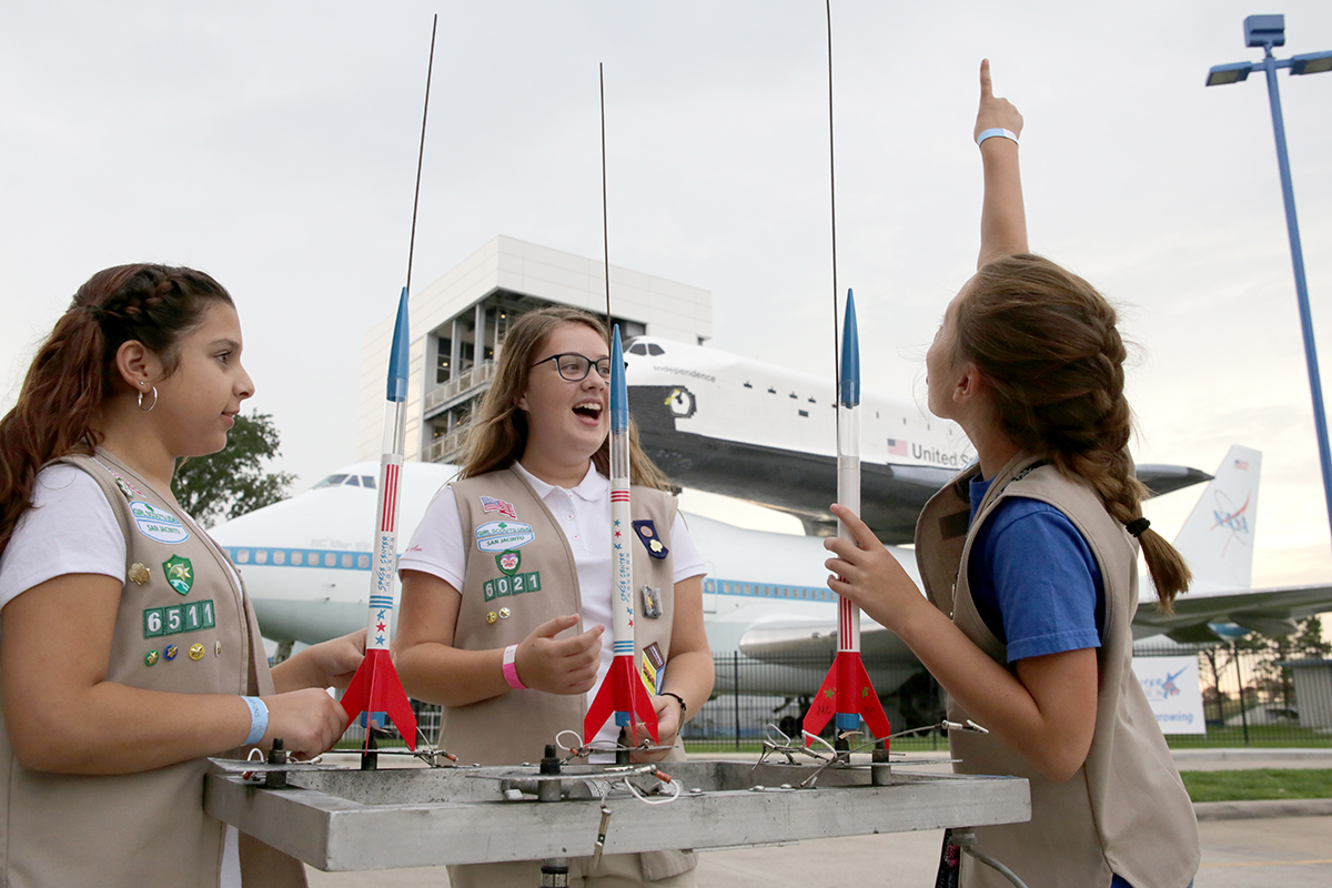 Girl scouts preparing for a rocket launch with Independence Plaza in the background.