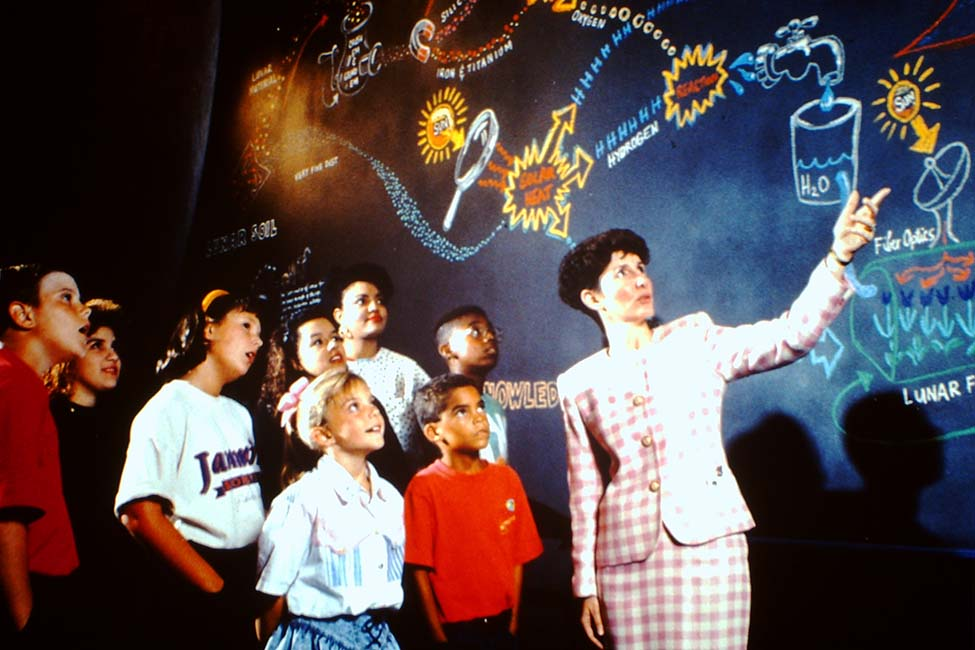 A teacher leads students on a tour of the center