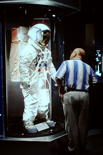A guest gazes at a spacesuit in Astronaut Gallery