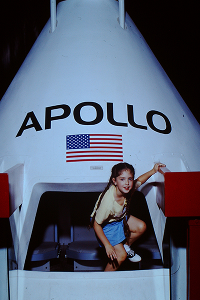 A young guest climbs out of an Apollo capsule replica