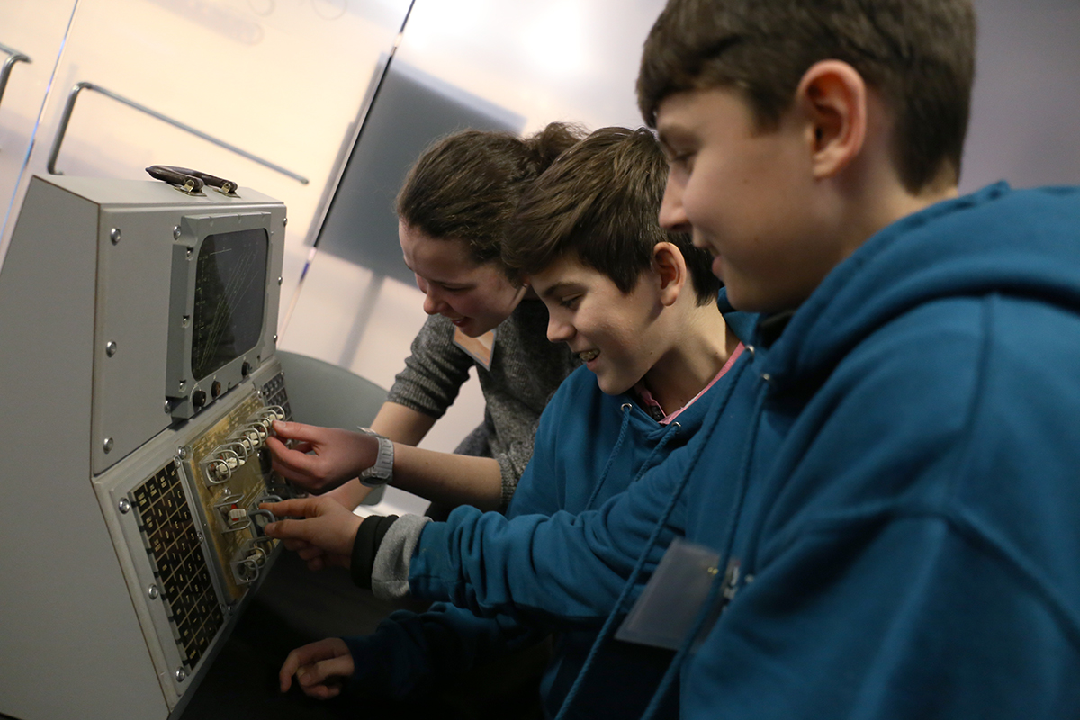 Students touch a model control panel.