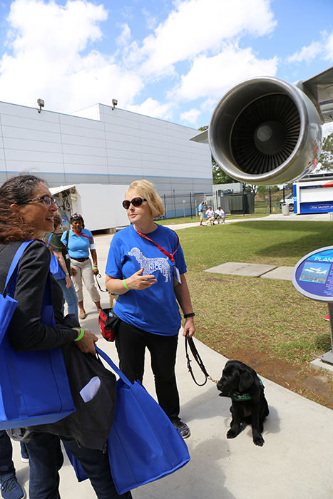 Guide dog and owner stand by plane engine in Independence Plaza