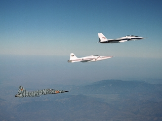 Northrop Grumman Corp.'s modified F-5E Shaped Sonic Boom Demonstration (SSBD) aircraft flies off the wing of NASA's F-15B Research testbed aircraft.