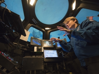 Maj. Anne McClain, one of two active-duty Army astronauts, stands inside a mock cupola at JSC.