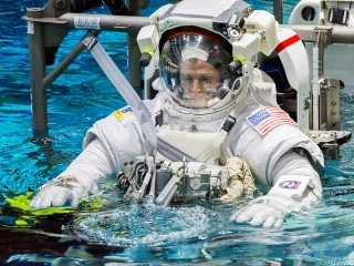 An astronaut is lowered into the pool at NASA's Neutral Buoyancy Lab to train for an ISS mission.