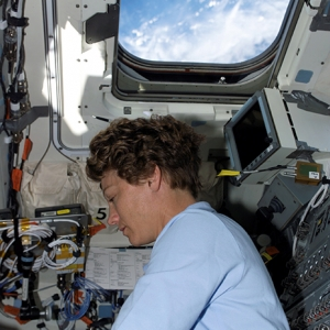 Astronaut Eileen M. Collins works aboard the shuttle orbiter Discovery.