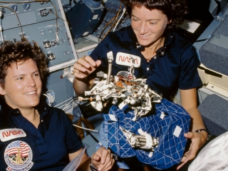 "Astronauts Kathryn D. Sullivan and Sally K. Ride show off a ""bag of worms."""
