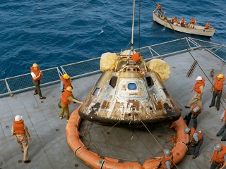The Apollo 11 capsule is recovered by the U.S.S. Hornet.