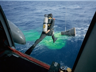 A Navy frogman leaps from a helicopter into the water to help recover the Gemini-12 capsule.