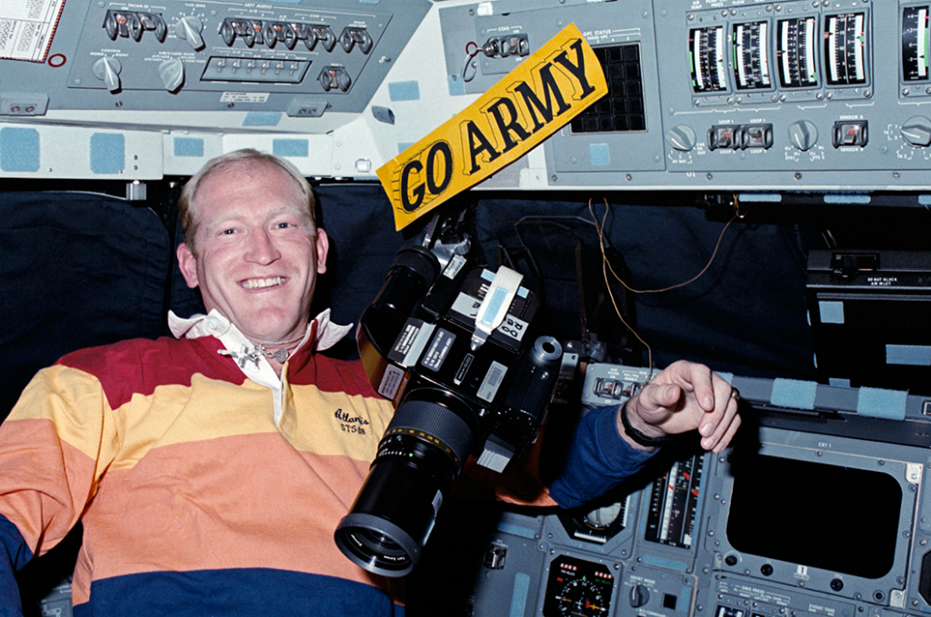 "Astronaut Charles D. Gemar floats next to a ""GO ARMY"" decal aboard Atlantis."