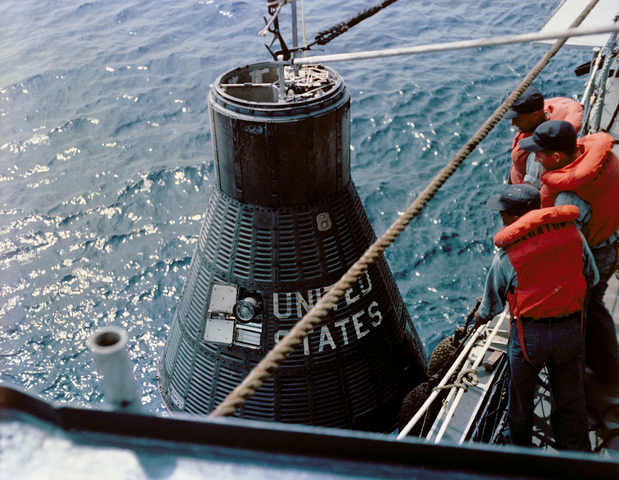 U.S. Naval sailors hoist up the MA-4 capsule onto the deck of the Decatur.