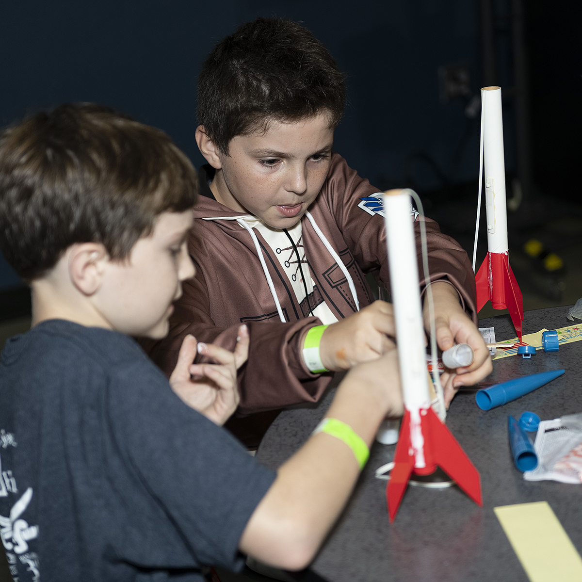 Kids assemble model rockets.