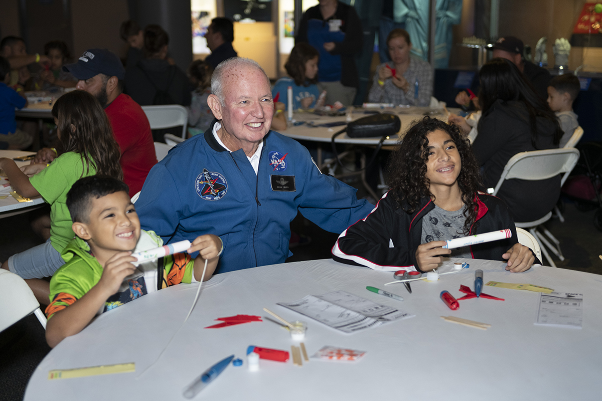 Astronaut helping campers build model rocket
