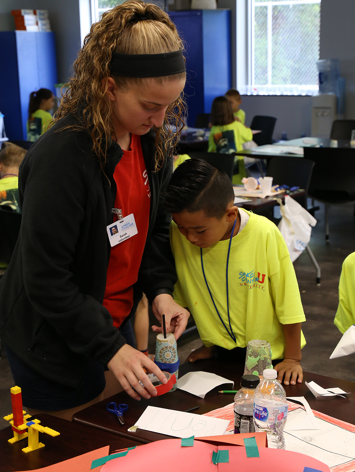 Volunteer helps students involved in an education program at the center.