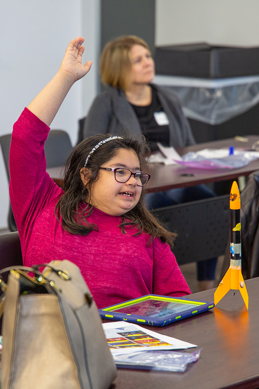 Student raises hand during Explorer Camp
