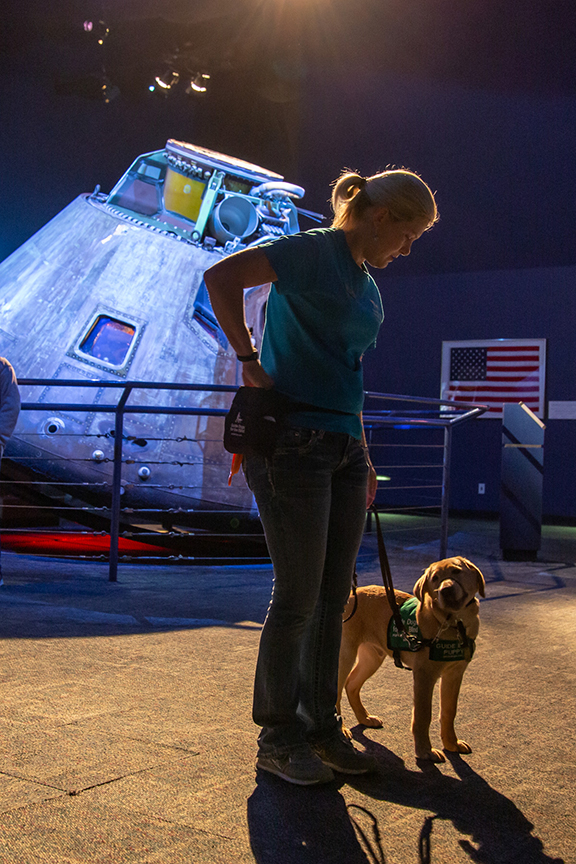 Visitor walks guide dog past Apollo 17 command module