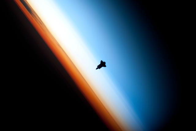 Endeavour's silhouette against Earth's colorful horizon.