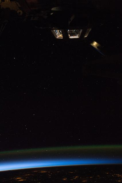 Cupola lights can be seen against the darkness of space as the sun begins to rise on the Earth below.