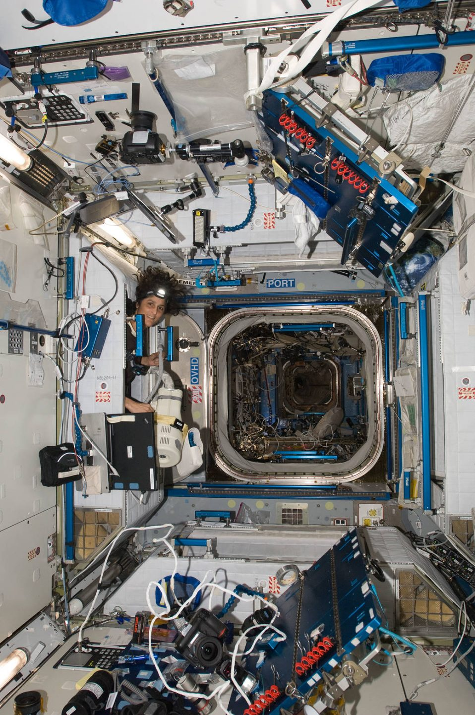 NASA astronaut Sunita Williams vacuums onboard the ISS during Expedition 33