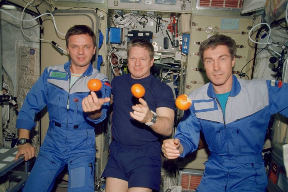 The Expedition One crew enjoys a treat of fresh oranges onboard the ISS.