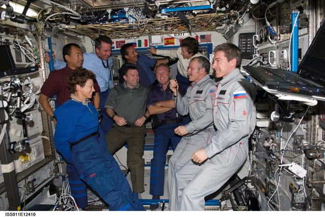 Expedition 11 and STS-114 crewmembers congregate in the Destiny laboratory onboard the ISS