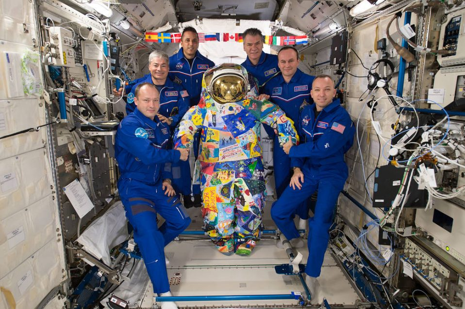 The crew of Expedition 53 poses with the VICTORY art spacesuit onboard the ISS