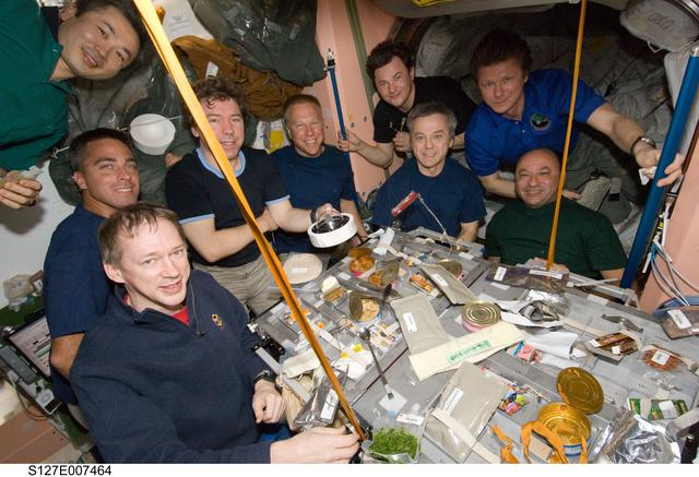 Expedition 20 and STS-127 crewmembers share a meal during joint operations onboard the ISS