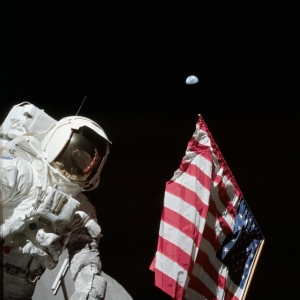 Scientist and NASA astronaut Harrison Schmitt poses next to an American flag on the Moon