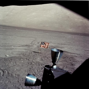 The American flag, planted on the surface of the Moon, is seen through the windows of the Lunar Module