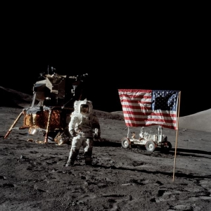Schmitt stands next to deployed American flag and Lunar Module on the surface of the Moon