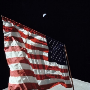 Apollo 17 crew photographs deployed American flag with Earth in background